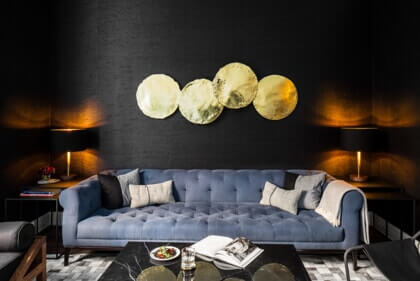 Black textured wall paper with blue couch and metal accent decor