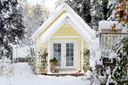 yellow outdoor she shed in the snow