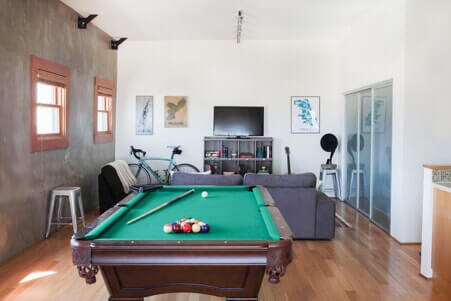 man cave with pool table, tv and couch