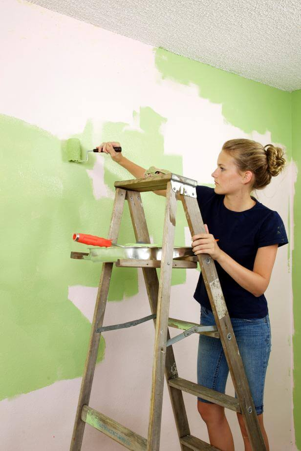 Woman painting a wall green